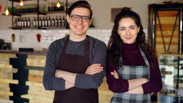 Portrait-of-two-coffee-house-owners-attractive-young-people-standing-inside-coffee-shop-smiling-and-looking-at-camera-Successful-start-up-and-beautiful-people-concept-