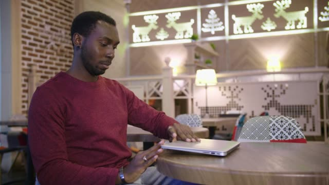 Portrait-of-happy-african-businessman-sitting-in-a-cafe-and-working-on-laptop