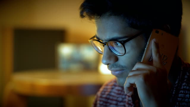 Close-up-Beautiful-Indian-Man-In-Glasses-Speaks-Over-Phone-And-Looks-At-Computer-Screen
