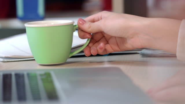 Business-woman-drink-coffee-in-office-Woman-hand-holding-green-coffee-cup