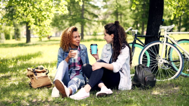 Cheerful-young-lady-is-talking-to-her-African-American-friend-and-drinking-takeout-coffee-in-park-on-nice-green-lawn-Girls-are-chatting-and-enjoying-drink-