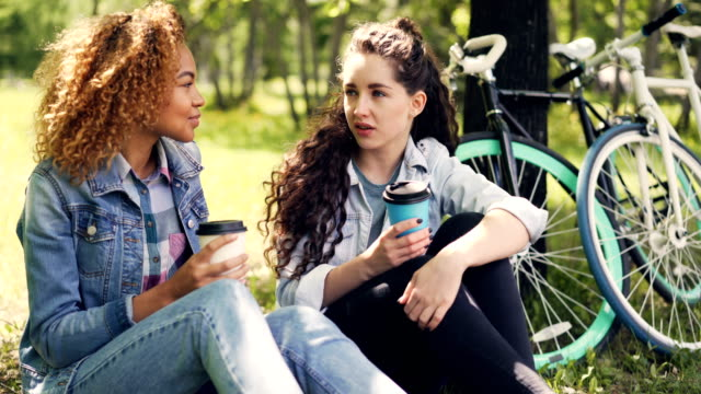 Female-students-are-chatting-and-drinking-to-go-coffee-in-park-resting-on-grass-after-riding-bikes-Attractive-girls-are-smiling-and-laughing-enjoying-drinks-