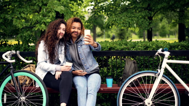 Best-friends-are-taking-selfie-with-smartphone-posing-for-funny-pictures-making-moustache-from-hair-then-hugging-and-taking-photos-Modern-lifestyle-concept-