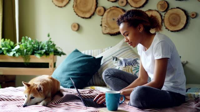 Chica-afroamericana-moderna-utiliza-laptop-y-beber-café-sentado-en-cama-con-Lindo-perrito-relajante-en-casa-Tecnología-concepto-de-personas-y-animales-domésticos-