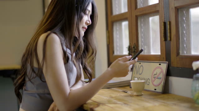 Asian-women-playing-phone-and-drinking-hot-coffee-in-coffee-shop-