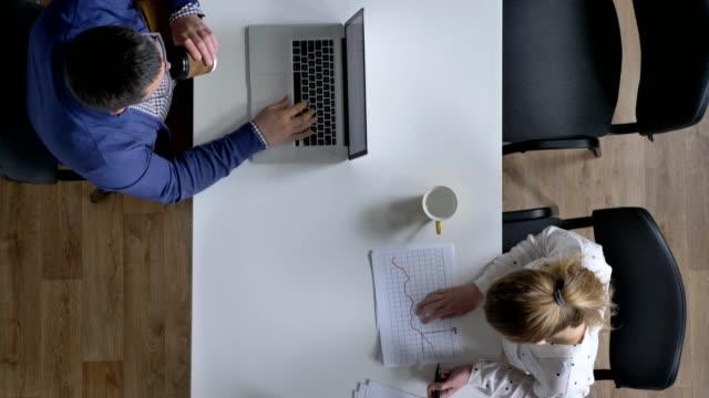 Cámara-moviendo-lentamente-por-encima-de-gente-trabajando-en-oficina-y-sentado-en-la-mesa-topshot