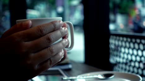 Woman-hand-holding-a-cup-of-coffee-in-the-cafe-in-the-rainy-day