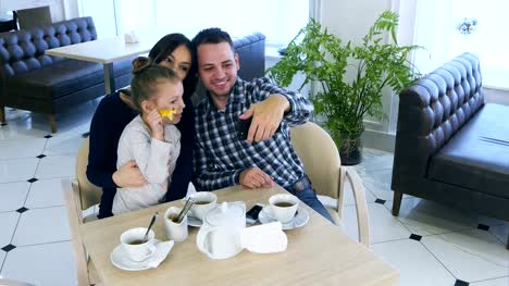 Happy-father-takes-selfie-photo-with-his-wife-and-daughter-during-their-tea-time-in-cafe-or-restaurant