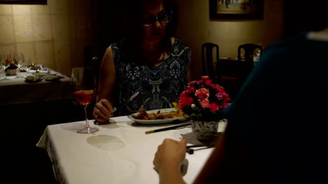 Im-Restaurant-eine-Frau-an-einem-Tisch-sitzen-Essen-reden-Gläser-Klirren-und-Rotwein-trinken
