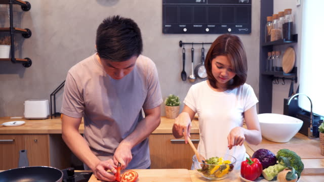 Man-hands-cutting-tomato-in-the-kitchen-Beautiful-happy-asian-couple-are-cooking-in-the-kitchen-Young-asian-couple-have-romantic-time-while-staying-at-home-Couple-lifestyle-at-home-concept-