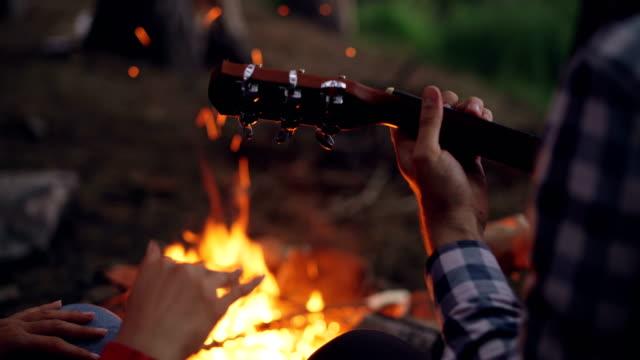 Toma-de-primer-plano-de-manos-hombres-tocando-la-guitarra-y-la-mujer-las-manos-en-el-baile-con-ardiente-fogata-en-fondo-Camping-concepto-de-música-y-gente-