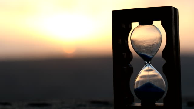 Hourglass-Passing-of-Time-Lapse-Clouds-An-hourglass-in-front-of-a-bright-blue-sky-with-puffy-white-clouds-passing-Time-concept-Sunset-time-Selective-focus