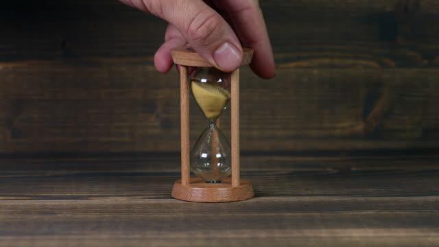 Sandglass-clock-on-wooden-table
