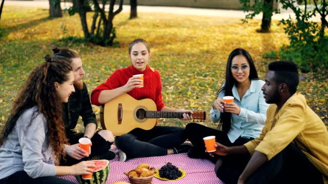Grupo-multiétnico-de-alegres-jóvenes-son-tintineantes-vasos-con-bebidas-y-beber-sentado-en-manta-en-el-césped-durante-otoño-picnic-con-comida-y-guitarra-