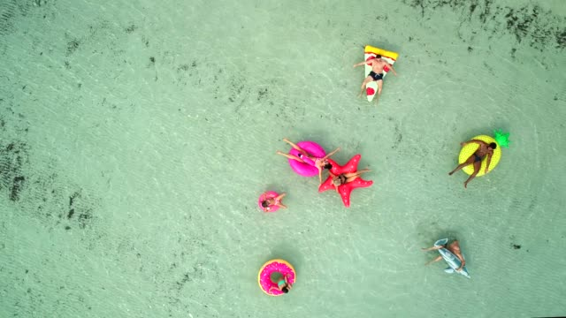 Aerial-view-of-friends-floating-on-inflatable-mattresses-in-transparent-sea-