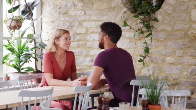 Mixed-race-young-adult-couple-sitting-at-table-talking-in-an-empty-restaurant