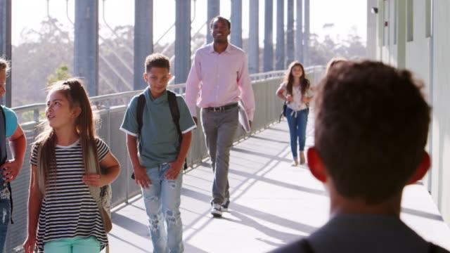 Jóvenes-de-la-escuela-los-niños-y-el-profesor-caminando-en-el-pasillo-de-la-escuela