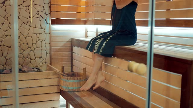 Girl-is-sitting-in-a-sauna-on-a-wooden-bench-with-bare-feet-Girl-relaxes-Span-camera-bottom-up-