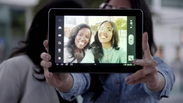 Screen-of-tablet-with-cheerful-multicultural-friends-taking-selfie