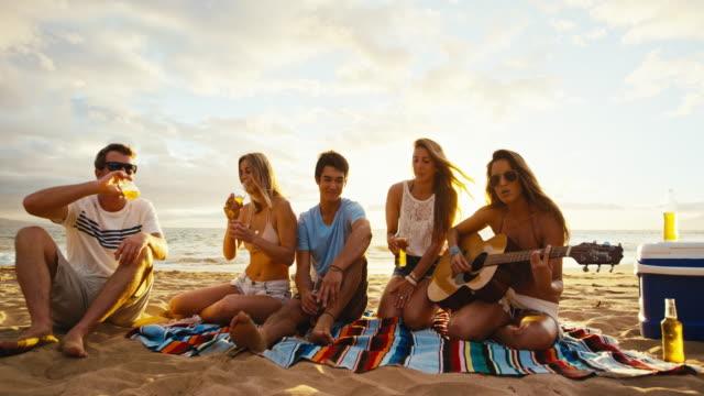 Amigos-relajantes-en-la-playa-al-atardecer