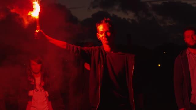Grupo-de-adolescentes-graves-con-una-celebración-y-agitando-rojo-señal-Flare-caminando-hacia-adelante-hacia-la-cámara-en-la-noche-