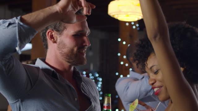 Pareja-de-raza-mixta-bailando-en-una-fiesta-de-cerca-disparada-en-R3D