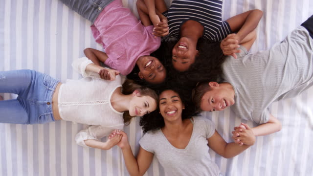 Overhead-View-Of-Teenage-Friends-Lying-On-Bed-Together