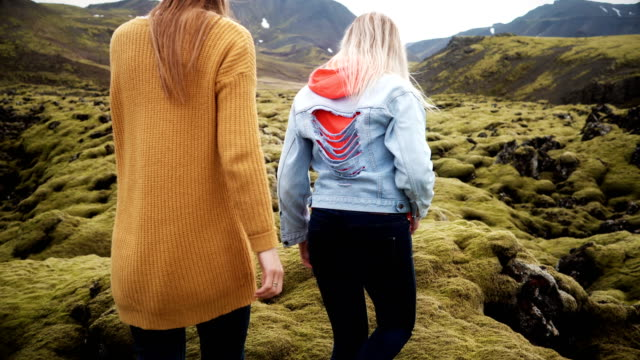 Back-view-of-two-tourists-woman-hiking-together-in-Iceland-Girls-walking-through-the-lava-field-covered-moss