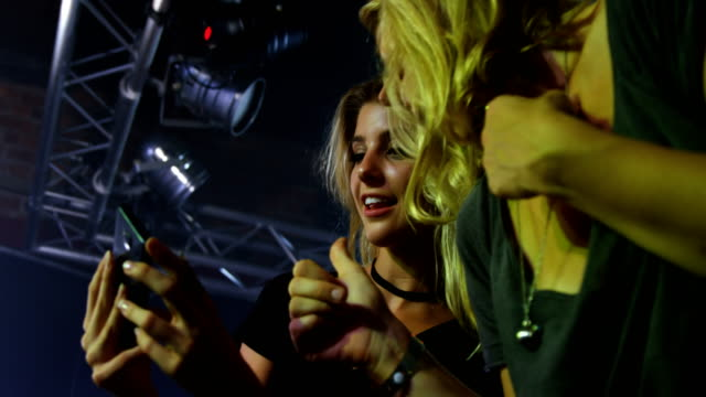Female-friends-reviewing-pictures-on-mobile-phone-at-a-concert-4k