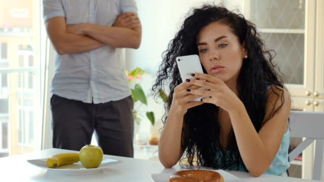Woman-uses-phone-sitting-at-table-funny-man-squats-at-the-background