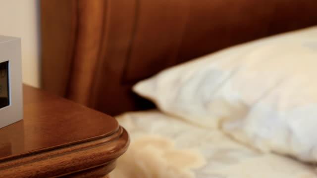 Electrónicos-alarma-de-reloj-en-la-mesita-de-noche-en-el-dormitorio
