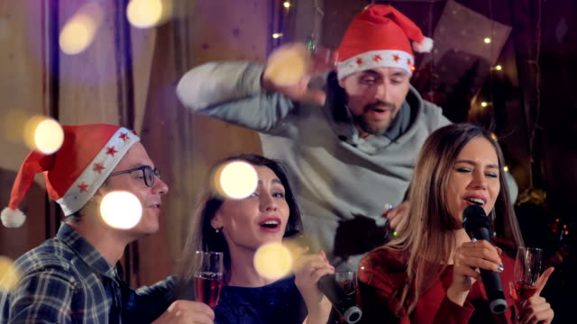 A-man-joins-two-singing-women-at-a-Christmas-party-