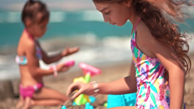 Niñas-en-vacaciones-de-verano-jugando-en-la-arena-de-la-playa