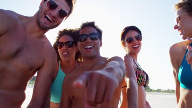 Multi-ethnic-friends-with-bodyboards-enjoying-the-beach