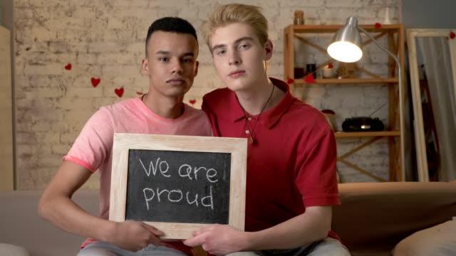 Eine-traurige-internationale-schwules-Paar-ist-auf-der-Couch-sitzen-und-einem-Namensschild-Wir-sind-stolz-darauf-Schauen-Sie-sich-die-Kamera-Wohnkomfort-im-Hintergrund-60fps