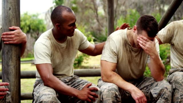 Militray-Soldaten-tröstet-ihre-Teamkollegen-im-Boot-Camp-4k