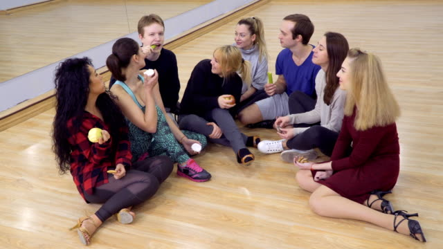 Group-of-young-friends-eats-snacks-one-after-another