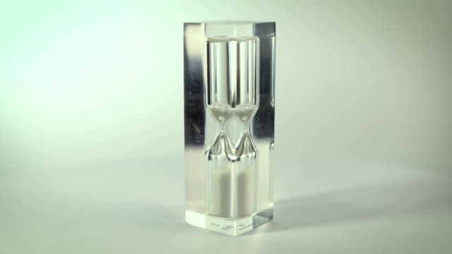 Modern-glass-hourglasses-rotate-against-a-white-background