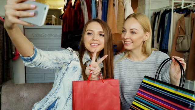 Primer-tiro-de-alegres-muchachas-con-bolsas-de-papel-haciendo-selfie-con-smartphone-mientras-está-sentado-en-el-Departamento-de-ropa-en-centro-comercial-Primero-que-estén-posando-luego-comprobación-de-imágenes