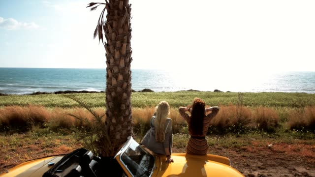 Young-women-sitting-on-retro-convertible-car-looking-at-sea