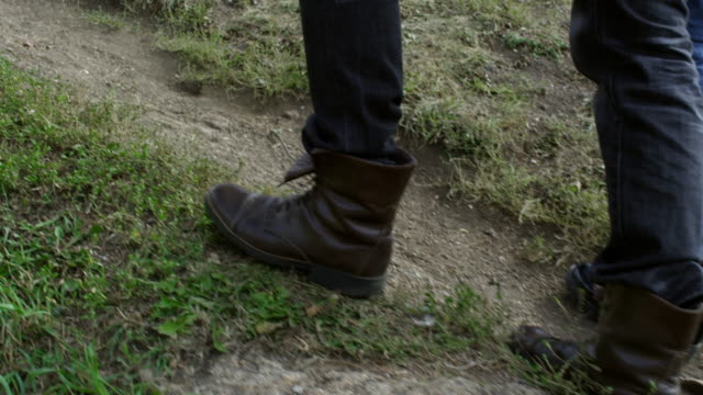 Piernas-de-excursionistas-irreconocibles-caminando-sobre-la-hierba