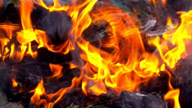 Slow-motion-smoke-of-fire-burning-garbage-on-dark-background-