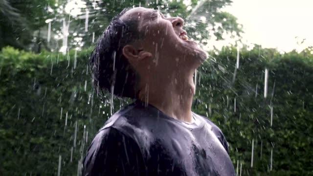 Retrato-de-joven-asiática-destacando-en-medio-de-la-lluvia-y-mirando-el-cielo-lleno-de-emociones-de-cerca-Tiempo-de-la-lluvia-fuera-de