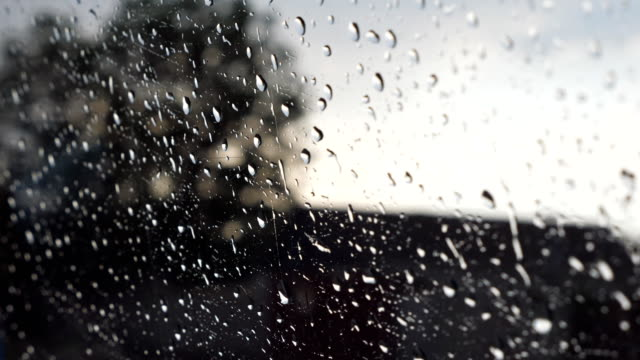 Close-up-of-raindrops-on-car-window-during-bad-weather-with-blur-background-Water-droplets-fall-on-the-glass-of-automobile-during-drive-at-countryside-POV-Slow-motion