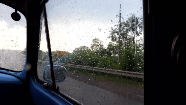 View-through-the-side-window-of-the-old-retro-car-while-moving-at-rainy-weather-Raindrops-falling-on-the-glass-of-vintage-automobile-during-drive-at-countryside-Close-up-Slow-motion