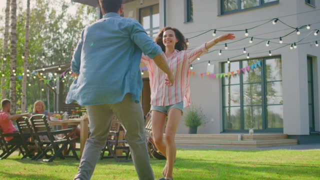 Beautiful-Young-Girl-Runs-Toward-Her-Boyfriend-He-Catches-Her-and-They-Hug-Spin-and-Dance-Together-Two-Young-People-Embrace-in-the-Backyard-of-a-Garden-on-a-Hot-Summer-Day-In-Slow-Motion-