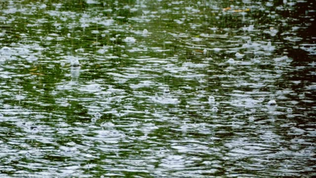 Heavy-tropical-rain-and-raindrops-falling-on-river-pond
