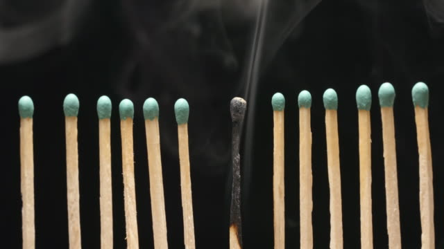 SLOW-MOTION:-Smoke-of-single-burned-matchstick-between-row-of-new-matchsticks
