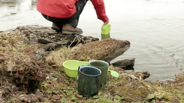 Excursionista-lava-los-platos-en-el-lago-Noruega