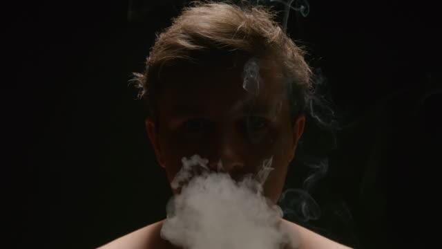 SLOW-MOTION:-Smoker-exhales-out-a-smoke